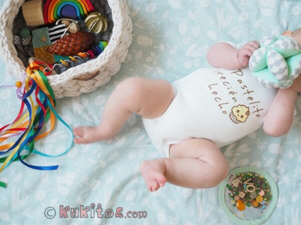 Un bebe jugando con la pelota Montessori y el cesto de los tesoros
